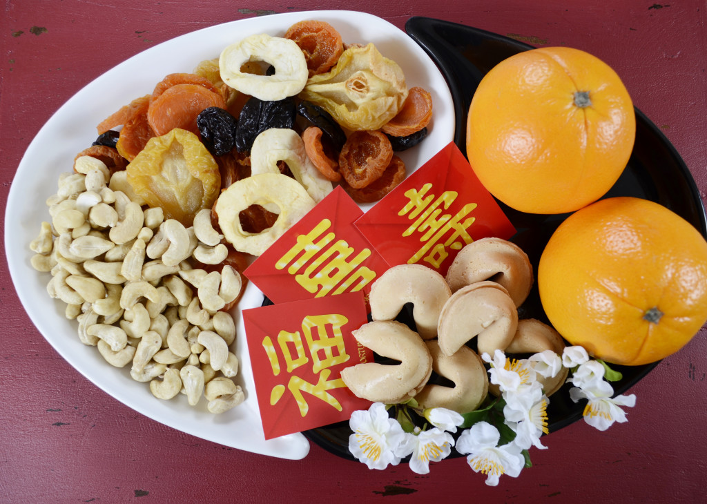 Happy Chinese New Year celebration party tray of togetherness on red wood background.